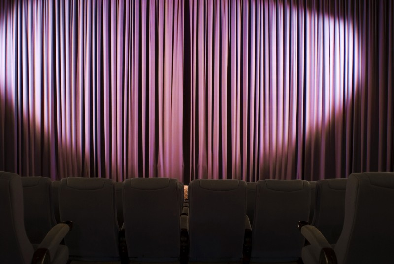 Darkened seats before a stage cutain lit by a large oval spotlight in a cinema or theatre